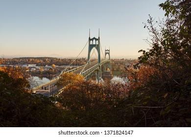 St. Johns Bridge over Willamette River in Portland Oregon at sunrise seen from Ridge Trail in Forest Park.