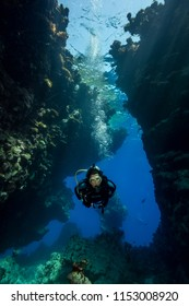 St John's caves, Red Sea, Egypt - August 2014: Woman diver explores the caves in the St John's reef area of the southern Red Sea