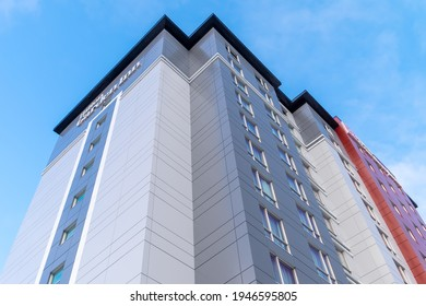 St. John's, Newfoundland  Canada - August 2020:Hilton Garden Inn hotel, a newly constructed, tall building with metal composite panels in grey, red and light grey against a bright blue sky and clouds.