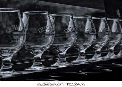 St. John's, Newfoundland/Canada - December 2018: A line of empty Quidi Vidi Brewery beer glasses on a window shelf.  The glasses have the microbreweries logo on the sampler.