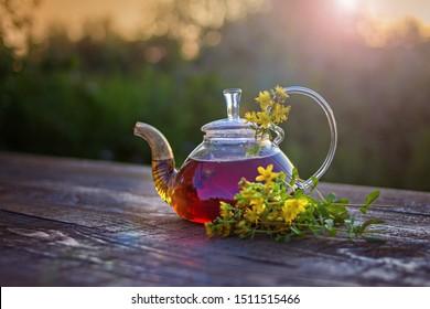St. John's wort flowers and tea in glass teapot on wooben table on sunset.