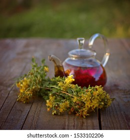 St. John's wort flowers and tea in glass teapot on wooden table on sunset.