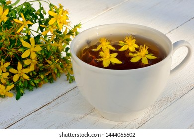 St. John's wort tea in a white cup on a white wooden background close-up