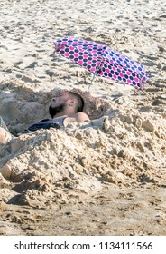 St Joseph MI USA , May 27 2018; A tired man relaxes in a cool hole dug in the sand, and under a shady polka dot umbrella