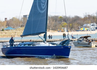 St. Joseph, Michigan, USA - May 4, 2019: Sail Boat leaving the harbor from St Joseph River and entering the Michigan Lake, passing by a fishing boat