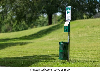 St. Joseph, Missouri / United States of America - August 30th, 2019 : Dog waste receptacle at the Corby dog park.  Includes bag dispenser and trash can.