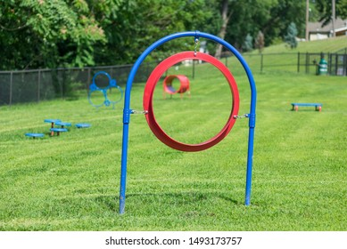St. Joseph, Missouri / United States of America - August 30th, 2019 : Dog agility equipment at the Corby Dog park.  A hoop, with other obstacles in the background.