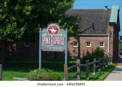 St. Joseph, Missouri / United States of America - August 29th, 2019 : Pony Express Museum sign, in the small park next door, with the museum in the background.