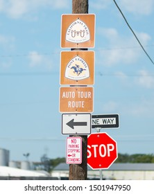 St. Joseph, Missouri / United States of America - August 29th, 2019 : California trail, Pony Express trail and Auto Tour route signs on a telephone pole, with a stop sign and one way sign