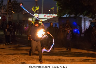St. Joseph, Missouri / United States of America - October 11th, 2019: A street performer uses flaming whips to make explosions and fireballs in front of a crowd during the Pony Express Pumpkinfest.