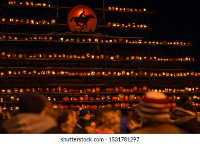 St. Joseph, Missouri / United States of America - October 11th, 2019: Rows of jack-o-lanterns lit up at night for the Pony Express Pumpkinfest.  Hundreds of pumpkins on display at night.