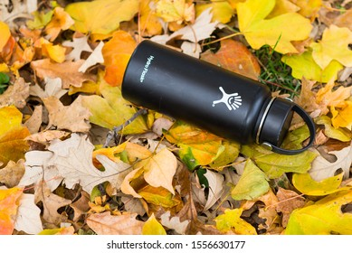 St. Joseph, Missouri / United States of America - November 3rd, 2019 : A Hydro Flask in black laying on a pile of leaves in autumn.  Reusable metal insulated beverage container on the ground.