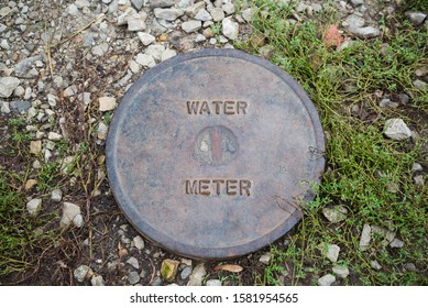 St. Joseph, MO / United States of America - October 21st, 2019 : Water meter metal cover on the ground, surrounded by plants, gravel, and dirt.  Heavy steel, with wear and rust.