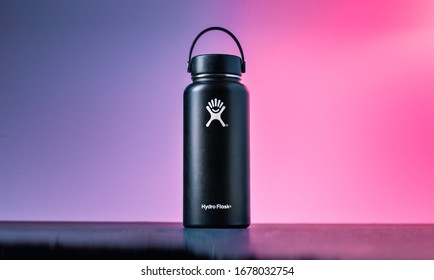St. Joseph, MO / United States of America - March 19th, 2020: Black Hydro Flask water bottle on pink and purple background.  Hero product shot of stainless steel reusable insulated beverage container.