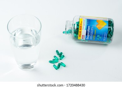 St. Joseph, MO / United States of America - May 1st, 2020 : A bottle of Ibuprofen gel caps open, with pills piled near a glass of water on a white surface.  CVS brand pain killers, liquid gel capsules