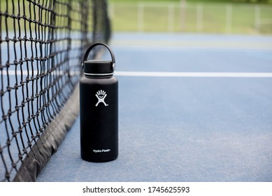 St. Joseph, MO / United States of America - May 24th, 2020 : Black Hydro Flask stainless steel reusable water bottle on ground near tennis court net.  Close up shot with room for copy on right.