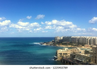 St Julian / Malta - September 2018: View over the the turuoise ocean of the bay at St Julian and the city in the background on a sunny afternoon on the 28th of September in Malta.