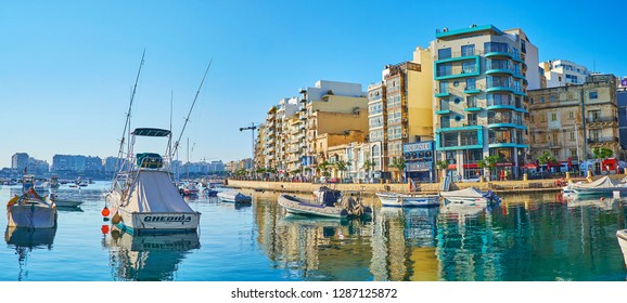 ST JULIANS, MALTA - JUNE 20, 2018: Panorama of the city with numerous power boats and George Borg Olivier street, reflected in calm waters of Spinola Bay, on June 20 in St Julians.