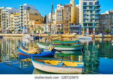 ST JULIANS, MALTA - JUNE 20, 2018: Spinola Bay harbor with colored wooden luzzu and modern motor boats, residential edifices and cafes along the promenade, on June 20 in St Julians.