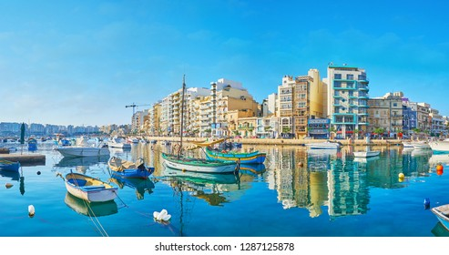 ST JULIANS, MALTA - JUNE 20, 2018: Panorama of the city coast from the Spinola Bay, occupied with moored fishing boats, on June 20 in St Julians.
