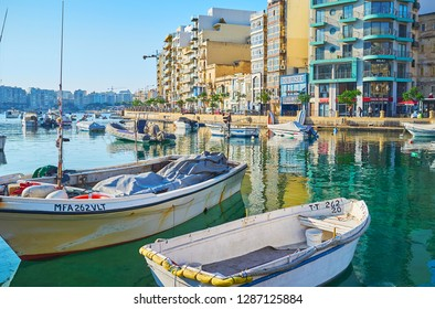 ST JULIANS, MALTA - JUNE 20, 2018: Walk along Spinola Bay and watch the bobbing boats and clear reflection on water surface, on June 20 in St Julians.