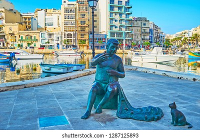 ST JULIANS, MALTA - JUNE 20, 2018: Maltese fisherman statue with net and cat, asking for the fish, stands at Spinola Bay with numerous fishing boats on background, on June 20 in St Julians.
