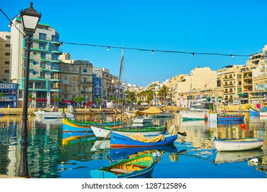 ST JULIANS, MALTA - JUNE 20, 2018: Traditional luzzu boats, docked in Spinola Bay harbor with a view on modern quarters on the background, on June 20 in St Julians.