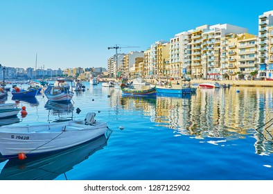 ST JULIANS, MALTA - JUNE 20, 2018: The calm waters of Spinola Bay harbor reflect the moored colored boats and modern residential buildings along its shore, on June 20 in St Julians.
