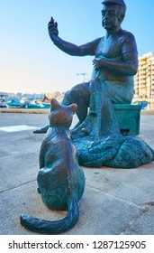 ST JULIANS, MALTA - JUNE 20, 2018: The modern statue of the fisherman and cat at Spinola Bay is the main landmark of the seaside promenade, on June 20 in St Julians.