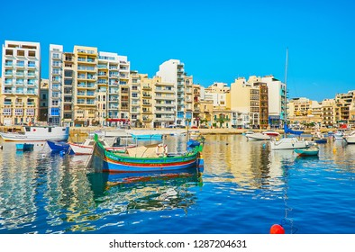 ST JULIANS, MALTA - JUNE 20, 2018: The line of modern residential buildings behind the Spinola Bay with many fishing boat, bobbing on the gentle waves, on June 20 in St Julians.