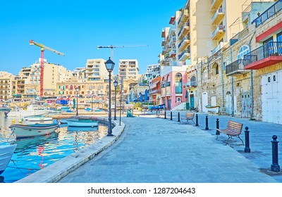ST JULIANS, MALTA - JUNE 20, 2018: Enjoy the morning shade in seaside promenade at Spinola Bay with a view on fishing boats, tourist restaurants and modern neighborhoods, on June 20 in St Julians.