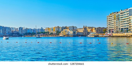 ST JULIANS, MALTA - JUNE 20, 2018: Panorama of the coast of Balluta Bay of St Julian's from the sea with a view on modern buildings and old Carmelite Church among them, on June 20 in St Julians.