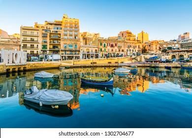St. Julians, Malta - November 11, 2015 : Small fishing boats moored in St Julians and Spinola bay on a sunny day in St Julians, Malta. St Julians is populer tourist destination in Malta.