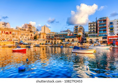 St. Julians, Malta - November 14, 2015 : Small fishing boats moored in St Julians and Spinola bay on a sunny day in St Julians, Malta. St Julians is populer tourist destination in Malta.