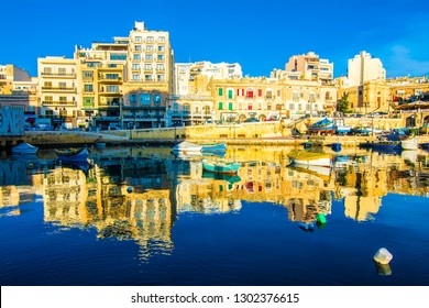 St. Julians, Malta - November 14, 2015 : Small fishing boats moored in St Julians and Spinola bay on a sunny day in St Julians, Malta. St Julians is populer tourist destination in Malta.