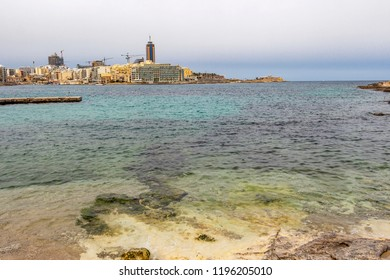 St. Julian's urban skyline with limestone shore in the foreground, at St. Julian's Bay, Malta