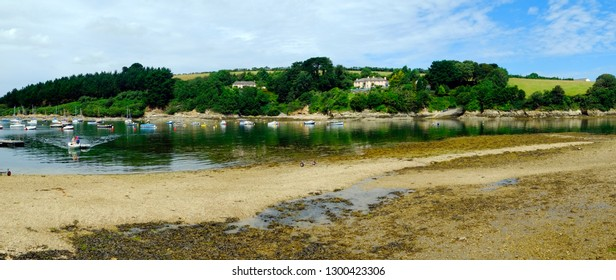 St Just in Roseland, UK - 25th July 2017: Low tide and a calm summer morning bring a few boats out onto the creek at St Just in Roseland on the picturesque Roseland Peninsula in Cornwall, UK