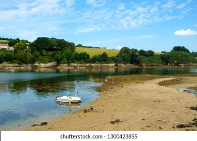 St Just in Roseland, UK - 25th July 2017: A calm summer morning brings people out to exercise their dogs by the creek at St Just in Roseland on the picturesque Roseland Peninsula in Cornwall, UK