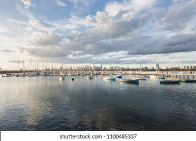 St. Kilda Pier with boats in the harbour, Melbourne, Australia. Melbourne CBD with financial towers are behind.