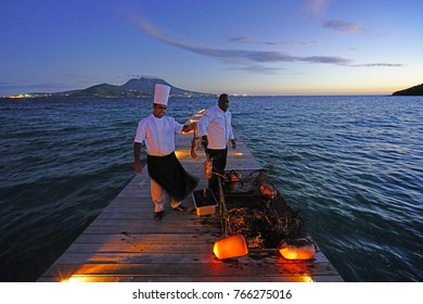 ST KITTS, ST KITTS AND NEVIS -19 NOV 2017- A chef picking a live lobster from a dock on the Caribbean Sea at the Park Hyatt St Kitts, a luxury upscale hotel resort in Christopher Harbor, Saint Kitts.