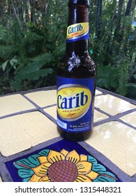 St. Kitts, St. Kitts and Nevis - December 22 2016: A bottle of Carib Beer on a table at a bar located in Romney Manor