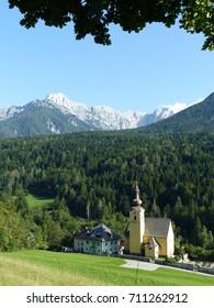 St. Leonard Catholic church at Fusine in Valromana, municipality Tarvisio, Italy. In the backround the Julian Alps.