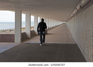 ST LEONARDS, UK - APRIL 13, 2017: a man walking away from camera in a covered walkway on the seafront promenade with strong leading lines front to back.