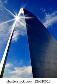 St. Louis Arch in Missouri with clouds and sky in background reflection of the sun