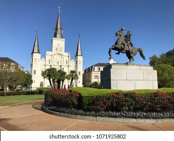 St. Louis Cathedral in Jackson Square, New Orleans, Louisiana. Color landscape photo of cathedral in background and Andrew Jackson statue in foreground with red flowers underneath statue.
