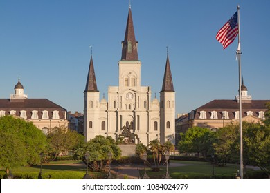 St. Louis Cathedral in Jackson Square within the French Quarter of New Orleans, Louisiana, USA. Golden morning light bathes the cathedral, American flag on right side of church, no people. Horizontal.