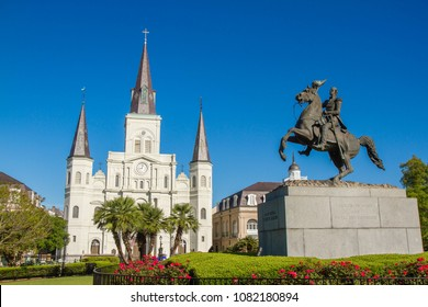 St. Louis Cathedral with statue of Andrew Jackson to the left of the cathedral, in the French Quarter of New Orleans, Louisiana, USA. Clear blue sky, red flowers under statue, no people, horizontal.
