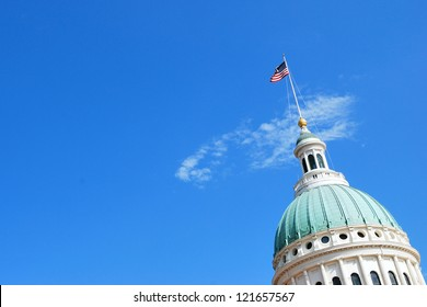 St. Louis Missouri Capitol with American flag against a sky.