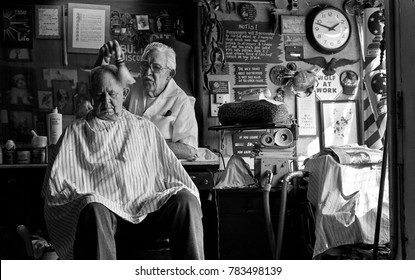 St Louis, Missouri, United States - circa 2007 - Old Man Barber Cutting Customers Hair in Vintage old-Fashioned Barbershop in rundown City Neighborhood