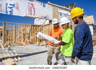 St. Louis, Missouri, United States-April 1, 2018-Three male construction workers, carpenters, wearing hardhats looking at blueprints at new residential subdivision home building work site